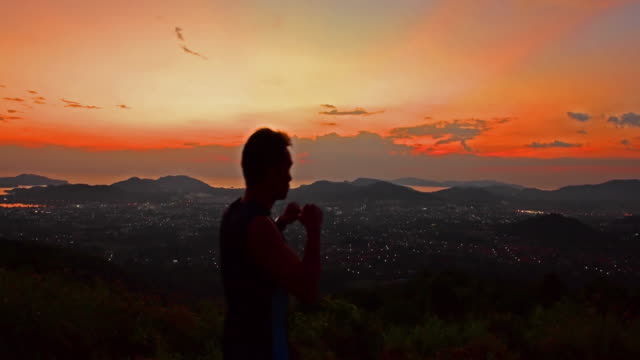 Young man  streches and exercise on hilltop field 4k.Young man  streches and exercise on hilltop field with sun set. pedal pushers stock videos & royalty-free footage