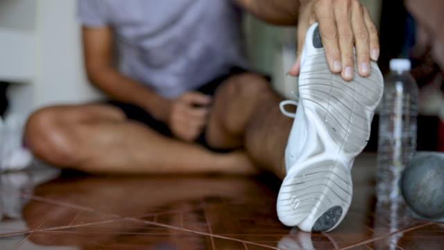 vídeos de stock e filmes b-roll de young man stretches the body before exercise - treino em casa