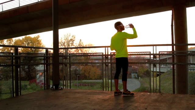 Young man stretching on a fence after jogging / exercising. Young man stretching on a fence after jogging / exercising. ankle stock videos & royalty-free footage