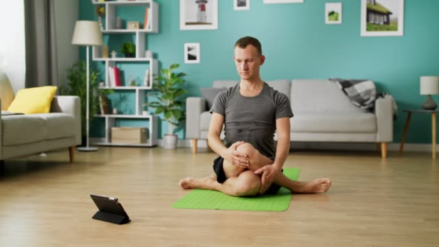 A young man studies yoga using instructions on a tablet video