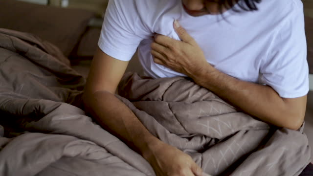 young man suffering from chest pain on the bed slow motion - torace umano video stock e b–roll