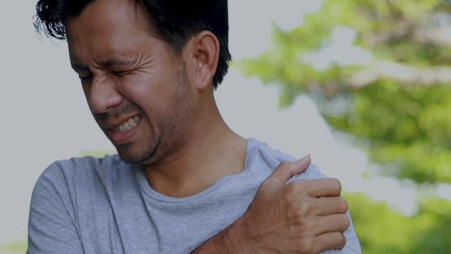 vídeos de stock, filmes e b-roll de homem novo que sofre da dor do ombro, conceito dos cuidados médicos - articulação humana
