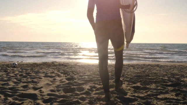 Young man surfer in wetsuit picks up surf board lying down on the sand at the beach and walks into the calm ocean water at sunset
