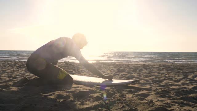junger mann surfer im neoprenanzug reiben decklack wachs paraffin auf surfbrett am sandigen strand bei sonnenuntergang vorbereiten - wachs epilation stock-videos und b-roll-filmmaterial