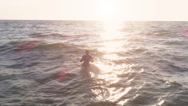 Young man surfer wearing wetsuit sitting on surf board floating in the calm ocean at sunset aerial view drone dolly
