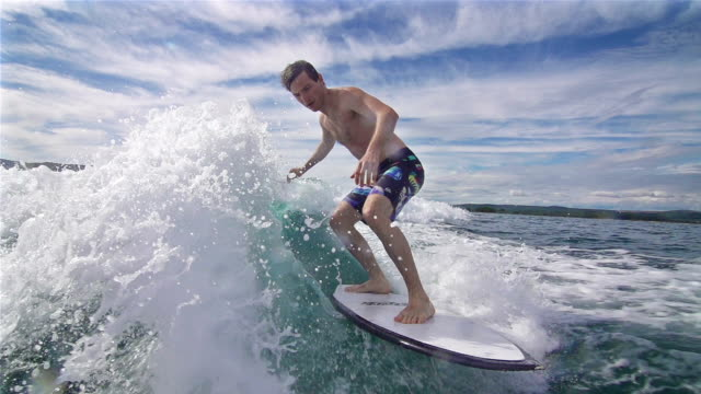 Young man surfing behind a boat video