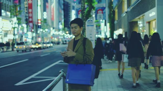 genç adam gece seyahat ve alışveriş için internette sörf - i̇yi giyimli stok videoları ve detay görüntü çekimi