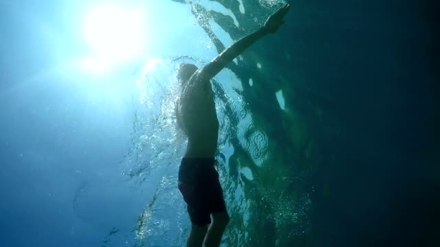 UNDERWATER: Young man swimming freestyle stroke in ocean above rocky coral reef video