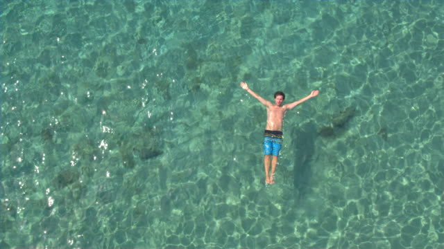 AERIAL: Young man swimming starfish float and relaxing in crystal clear ocean video