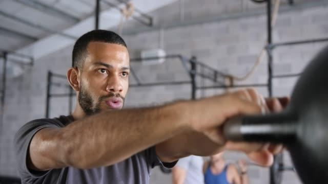slo mo jüngling schwingt die kettlebell im fitness-center - fitnessausrüstung stock-videos und b-roll-filmmaterial