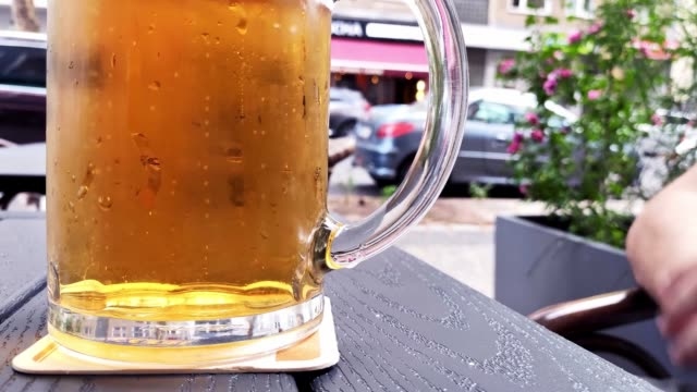 a young man takes a beer in his hands. - leva video stock e b–roll