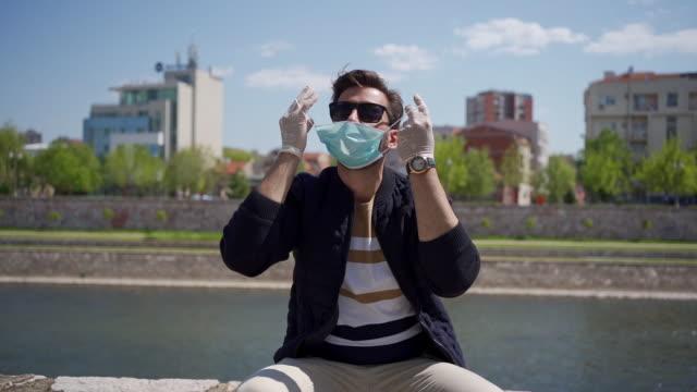vídeos de stock e filmes b-roll de a young man takes off her protective mask - remover