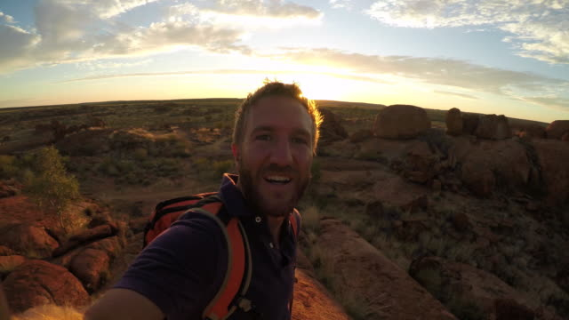 Young man takes selfie portrait with spectacular landscape at sunrise-4K video