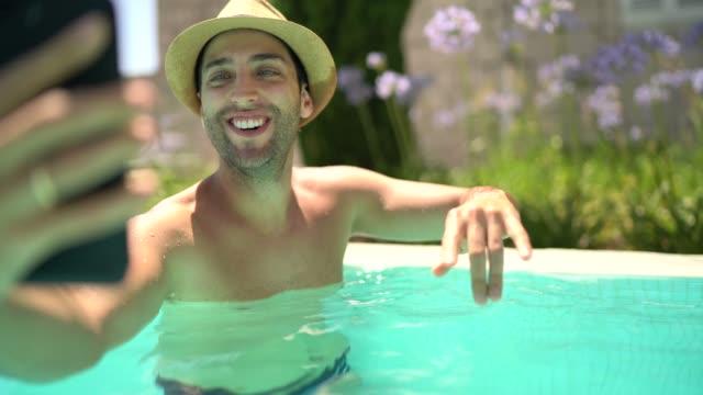 수영장에서 셀카를 찍는 젊은 남자 - influencer 스톡 비디오 및 b-롤 화면