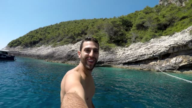 Video Young man taking a selfie jumping at Hvar coastline, Croatia