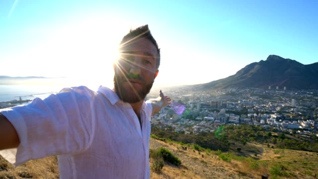 Young man taking selfie portrait in Cape Town at sunrise Young man taking selfie portrait in Cape Town at sunrise table mountain national park stock videos & royalty-free footage
