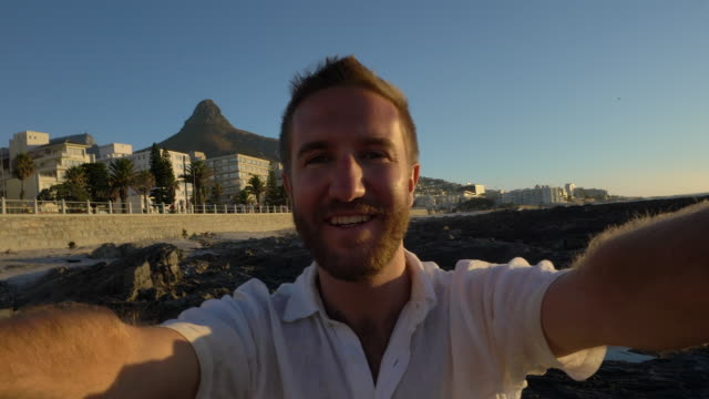 Young man taking selfie portrait in Cape Town, sunset video