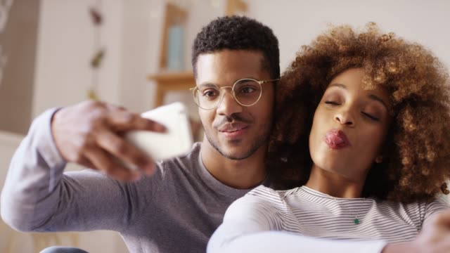 young man taking selfie with woman in bedroom - fare la lingua video stock e b–roll