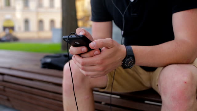 Young man talking on mobile phone on a bench in the city video
