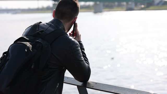 Young man talking on phone by the river in the city video