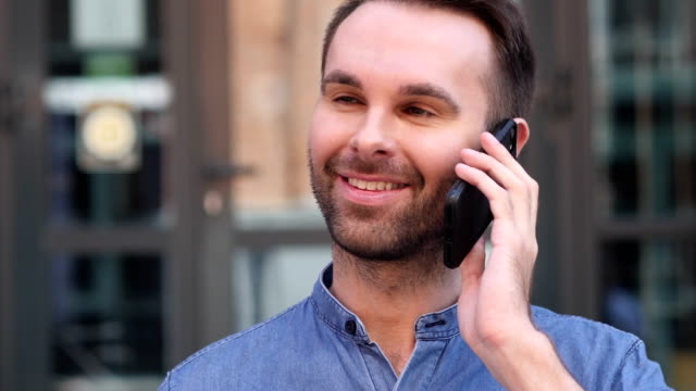 Young Man Talking on Phone, Negotiating in Good Mood video