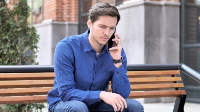 young man talking on phone, sitting outdoor on bench - rispondere video stock e b–roll