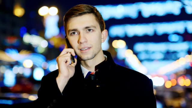 A young man talking on the phone, smiling, then looks into the camera video