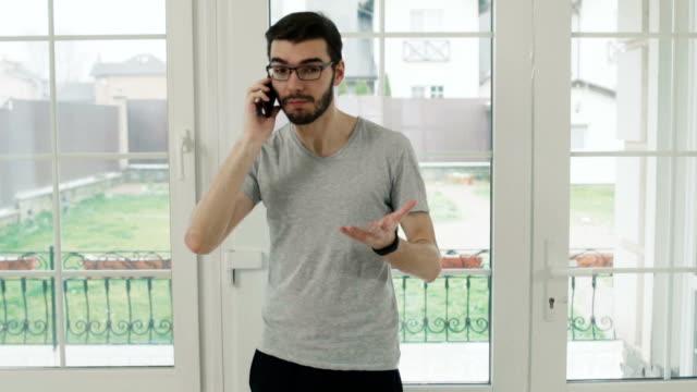 ung man samtal på telefon och skriker på samtalspartner - unga män bildbanksvideor och videomaterial från bakom kulisserna