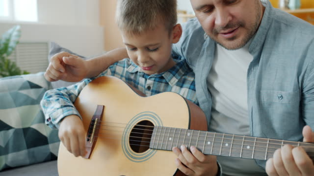 Young man teaching son play the guitar enjoying creative activity indoors in apartment video