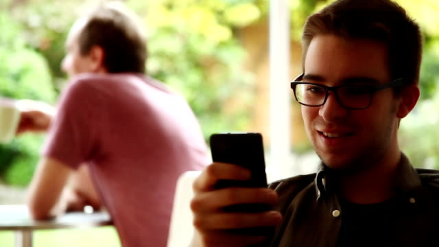 Young man texting in internet cafe. video