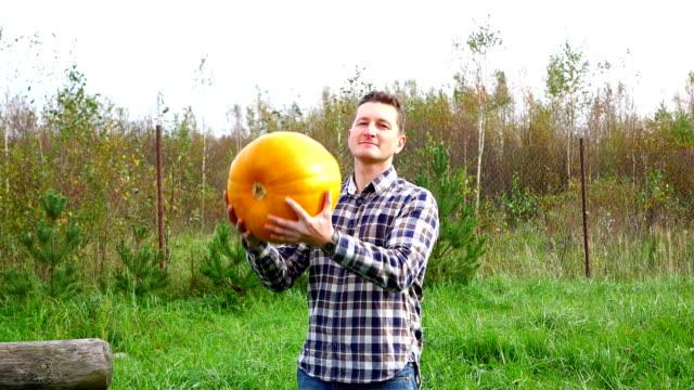 Young man throw up in air orange pumpkin, good crop, slow motion video
