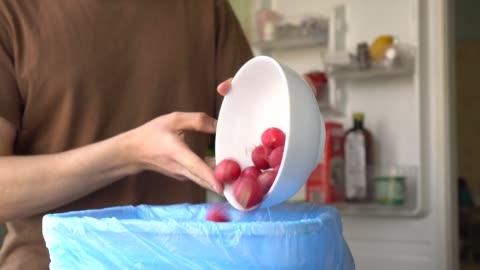 stockvideo's en b-roll-footage met jonge man gooit bedorven groenten uit de koelkast. huishoudelijk voedsel afval in de prullenbak - dranken en maaltijden