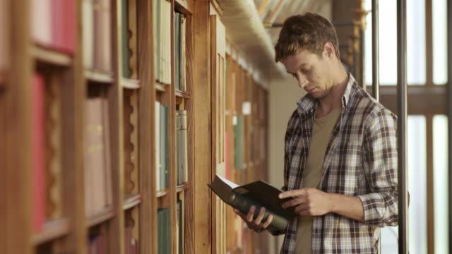 vídeos y material grabado en eventos de stock de pan young man thumbing a través de un libro en la biblioteca - biblioteca