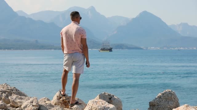 Young man tourist enjoying looking to sea beach mountains in Kemer Young man tourist enjoying looking to sea beach mountains in Kemer saturated color stock videos & royalty-free footage