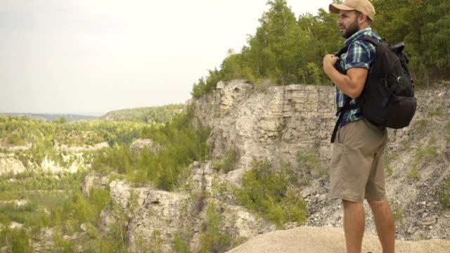junger mann tourist sucht in der ferne auf einen abgrund stehend. - faul ast stock-videos und b-roll-filmmaterial