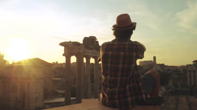 young man tourist sitting at roman forum at sunrise taking picture with vintage camera. historical imperial foro romano from panoramic point of view, italy - coloniale video stock e b–roll