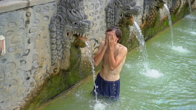 Young man tourist visits the famous Banjar Hot Springs on the Bali island. Bali Travel Concept. Slowmotion shot