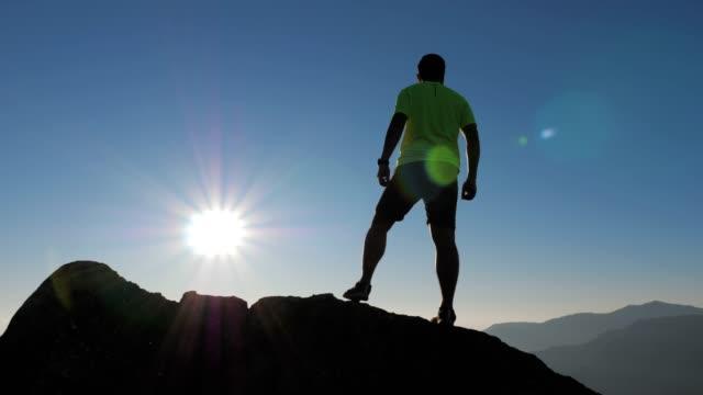 ung man leden löpare kör på toppen av berget, slowmotion - jogging hill bildbanksvideor och videomaterial från bakom kulisserna