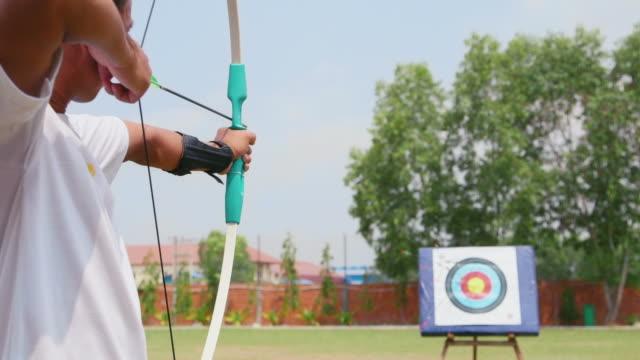 vidéos et rushes de jeune homme entraînement au tir à l'arc, personnes, sport, loisirs, activités de loisirs - tir à l'arc
