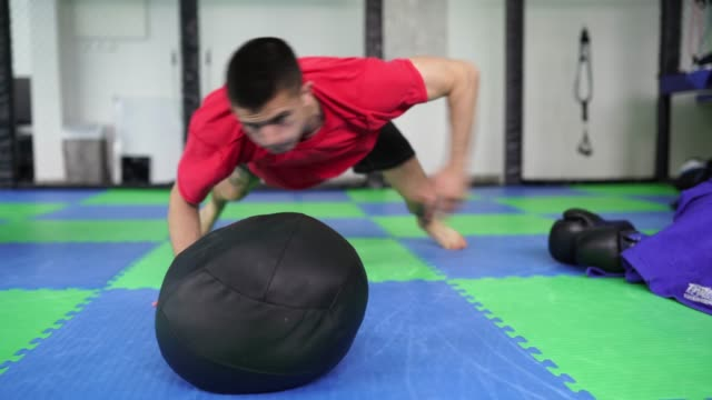 Young man training hard in gym One man training hard on the floor in gym. macho stock videos & royalty-free footage