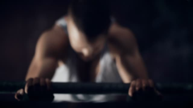 young man training on chin-up bar in gym - rivalità video stock e b–roll