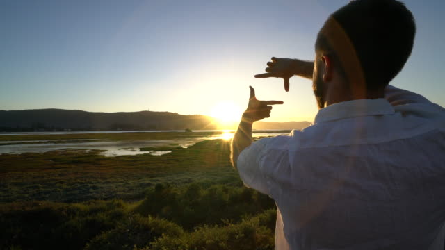 Young man traveling frames sunset with hands video