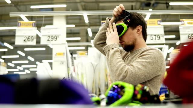 young man try on snowboard glasses in the supermarket - negozio sci video stock e b–roll