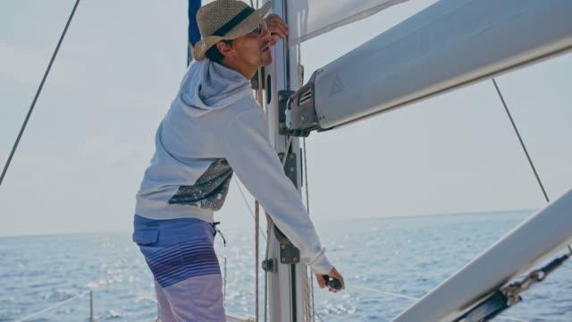 4K Young man turning crank, lowering sailboat sail, real time 4K Young man turning crank, lowering sailboat sail. MS, pan up, real time. crank mechanism stock videos & royalty-free footage