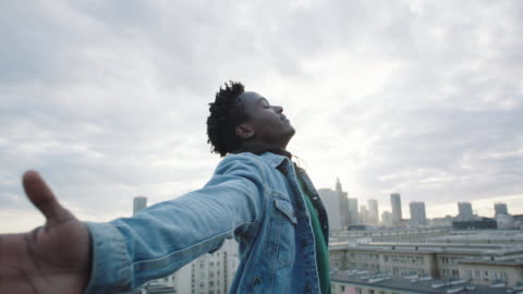 Young man turning on roof with opening arms . African man closed eyes. Cityscape in the background cultures stock videos & royalty-free footage