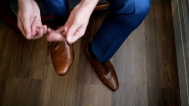 A young man tying elegant shoes indoors, close up video