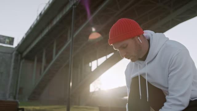 giovane uomo legare i lacci delle scarpe prima di iniziare l'allenamento quotidiano di routine. uomo che fa esercizi e si riscalda prima della corsa e test di fitness fisico sul ponte. - annodare video stock e b–roll