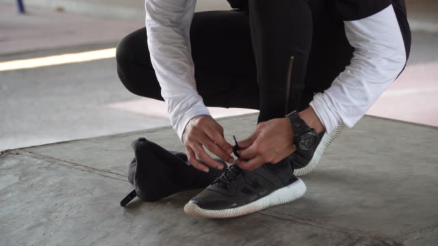 A young man tying shoe lace Tilt up shot of a young man tying shoelace and wear black cap wristwatch stock videos & royalty-free footage
