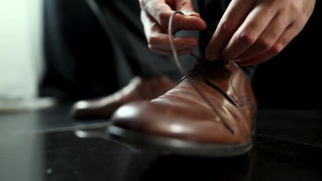 靴ひもクローズアップを結ぶ若い男 - 靴点の映像素材/bロール