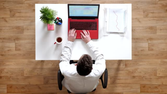 young man typing on keyboard, closing laptop and walking away, topshot, sitting behind desk - vicino video stock e b–roll